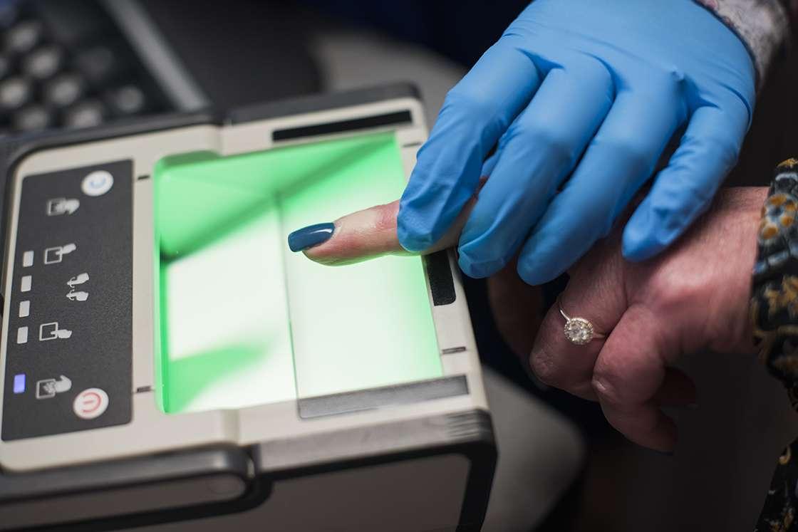 A gloved hand scans a finger for fingerprinting.
