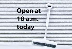 "Snow-covered shovel with text: ""Open at 10 a.m. today"""